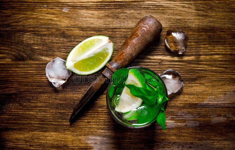 Szkło koktajl, lód, nóż i plasterki wapno na drewnianym stole chłodno, obrazy stock