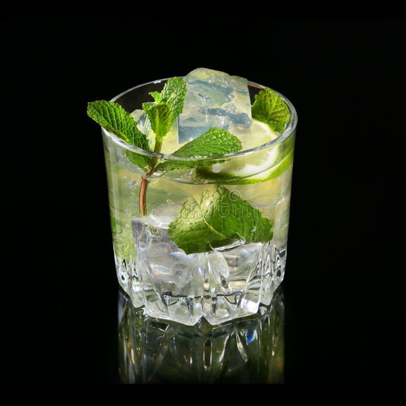 Szkło koktajl z rumem, wapno, kostka lodu i nowi liście na czerni, odzwierciedlamy tło zdjęcia stock