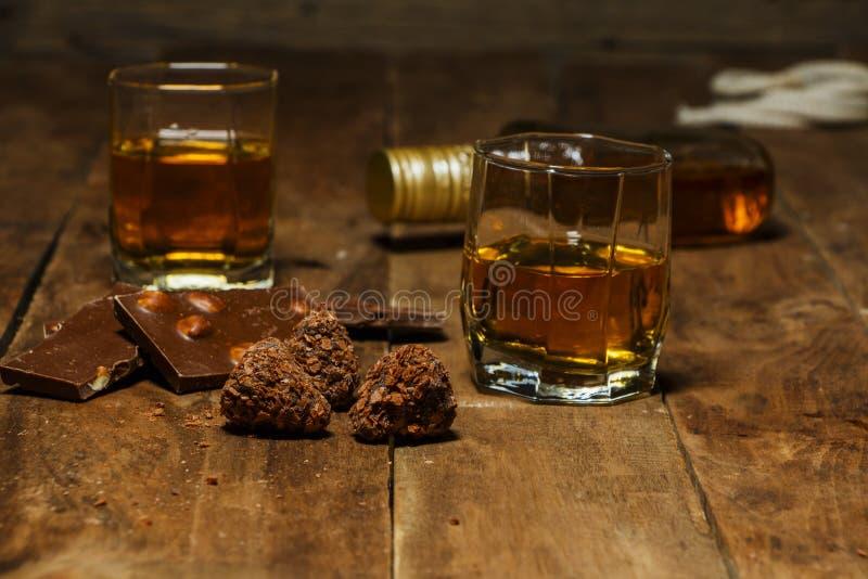 Szkło koniak lub whisky na nieociosanym stole z czekoladą fotografia royalty free