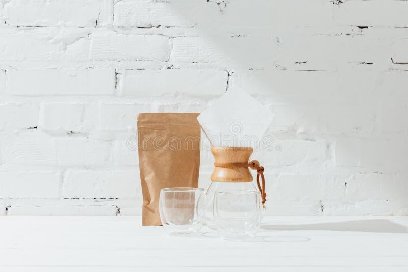 Szkło kubki, chemex i papierowy pakunek z kawą, obrazy stock