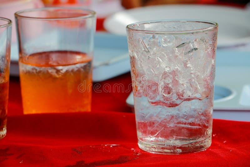 Szkło lód jest na stołowej czerwonej tkaninie zdjęcie royalty free