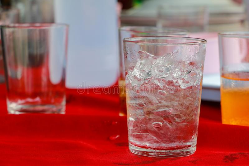 Szkło lód jest na stołowej czerwonej tkaninie fotografia royalty free