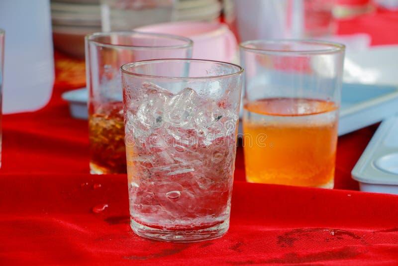 Szkło lód jest na stołowej czerwonej tkaninie zdjęcia stock