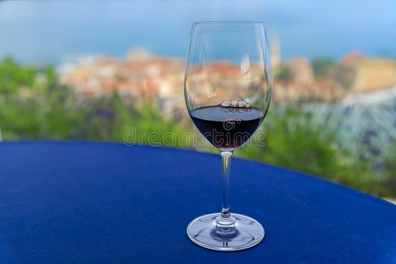 Szkło lokalny czerwone wino na stole przy restauracją z Budva Starym miasteczkiem i Adriatyckim morzem w Montenegro w tle obraz royalty free