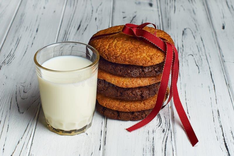 Szkło mleko i ciastka wiązał z czerwonym faborkiem obrazy royalty free