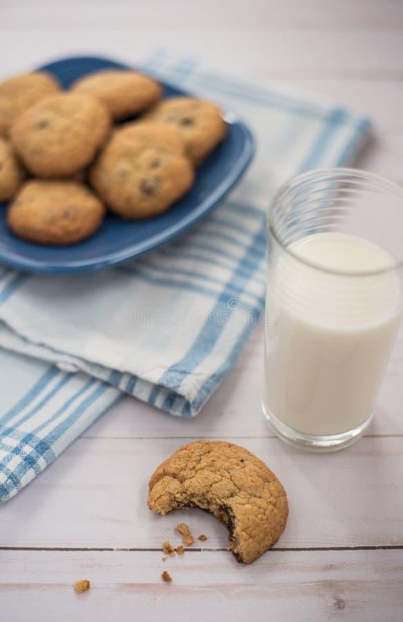 Szkło mleko i ciastko z kąskiem brać z go obok zdjęcie royalty free