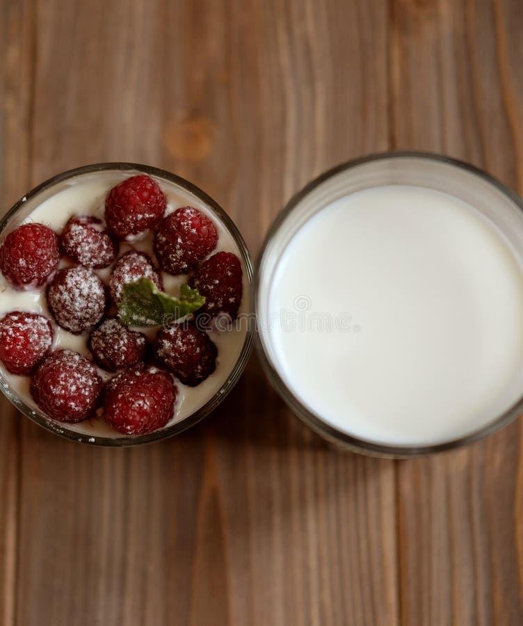 Szkło mleko i granola z malinkami nad drewnianym tłem, odgórny widok, zakończenie up obraz stock