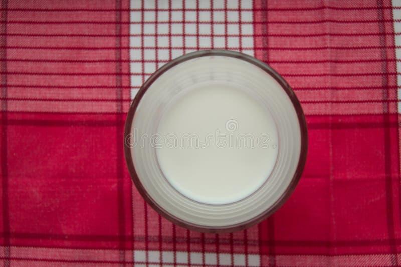 Szkło mleko stojaki na czerwonym w kratkę płótnie, odgórny widok obrazy stock