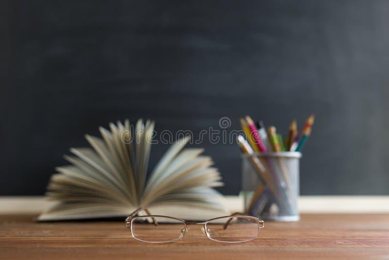 Szkło nauczyciel rezerwuje i stojak z ołówkami na stole na tle blackboard z kredą, Pojęcie teac obraz stock
