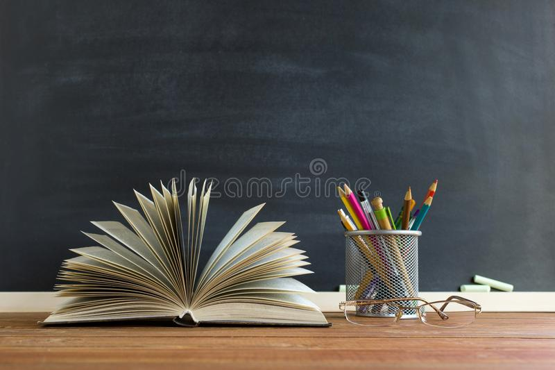 Szkło nauczyciel rezerwuje i stojak z ołówkami na stole na tle blackboard z kredą, Pojęcie teac zdjęcie stock