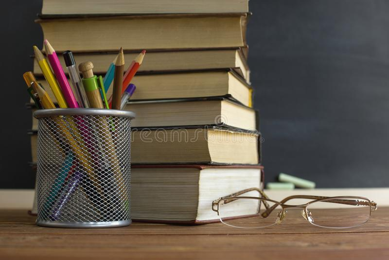 Szkło nauczyciel rezerwuje i stojak z ołówkami na stole na tle blackboard z kredą, Pojęcie teac obraz royalty free