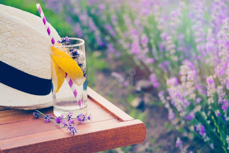 Szkło odświeżająca lemoniada i słomiany kapelusz nad drewnianym krzesłem Kwitnąca lawenda kwitnie w tle zdjęcia royalty free