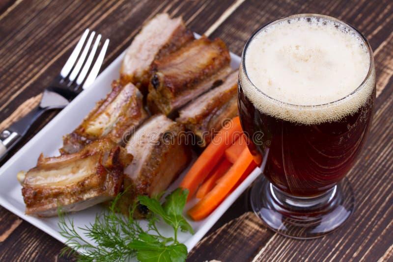 Szkło piwa I wieprzowiny ziobro Z marchewką Na Drewnianym tle obrazy stock