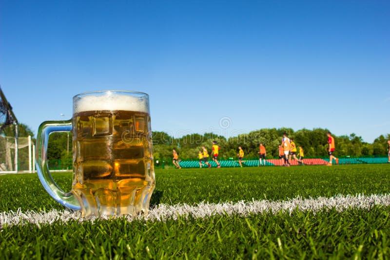 Szkło piwo jest na boisku piłkarskim, futbol bawić się w stadium obrazy stock