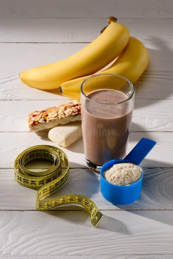 szkło proteinowy potrząśnięcie z bananami i energetycznymi barami na bielu zdjęcia stock