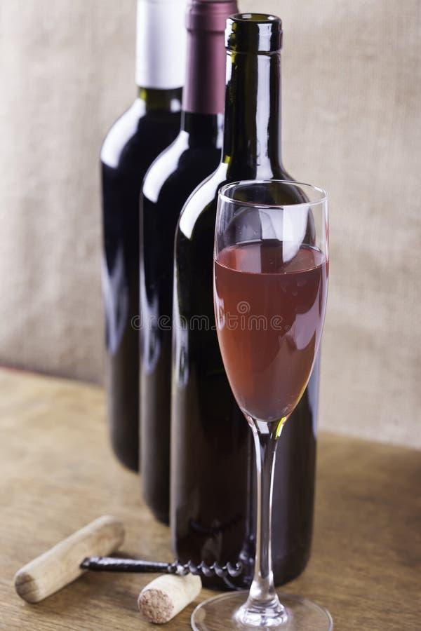 Szkło różany wino, corkscrew na tło butelkach obrazy royalty free