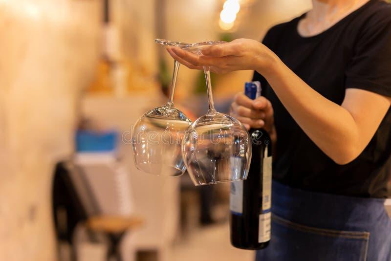 Szkło skrzydło w kelnerce jest ręką z butelki czerwonym winem w tle obraz stock
