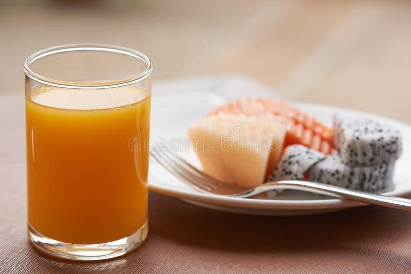 Szkło sok pomarańczowy i talerz owoc na stole fotografia royalty free