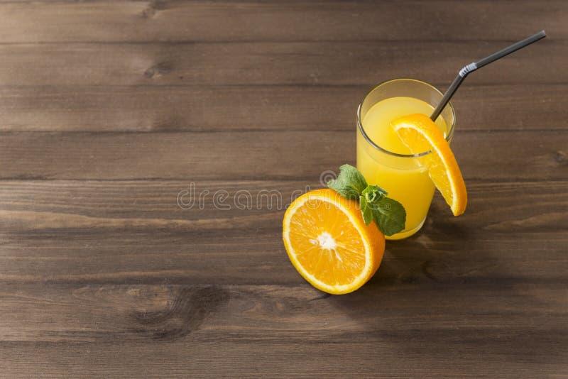 Szkło sok pomarańczowy z mennicą, połówka świeżej pomarańcze, plasterek pomarańcze na szkle z tubką zdjęcia royalty free
