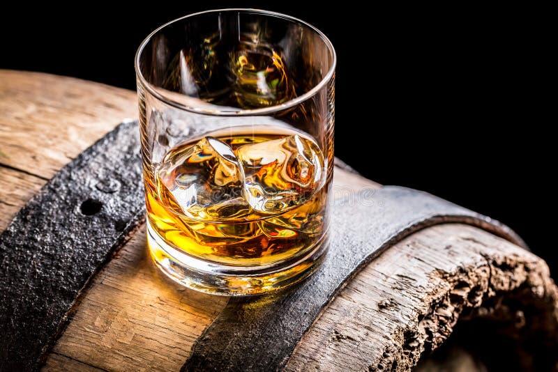 Szkło whisky i stara drewniana baryłka obraz royalty free