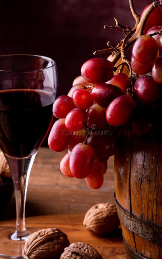 Szkło wino i czerwoni winogrona na baryłce obrazy stock