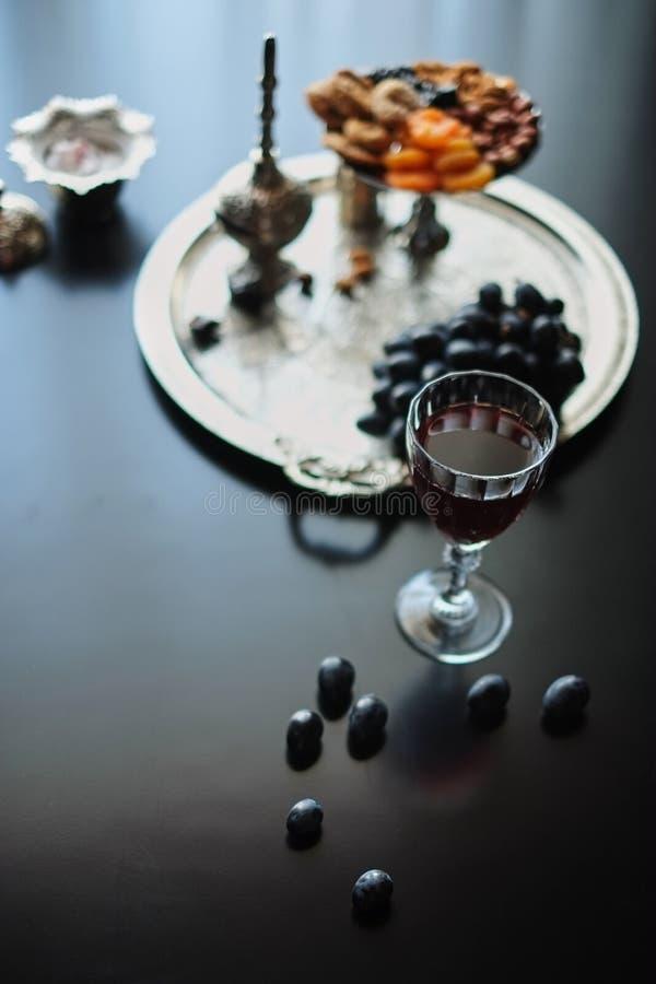 szkło wino i wysuszone owoc czernimy tło zdjęcie royalty free