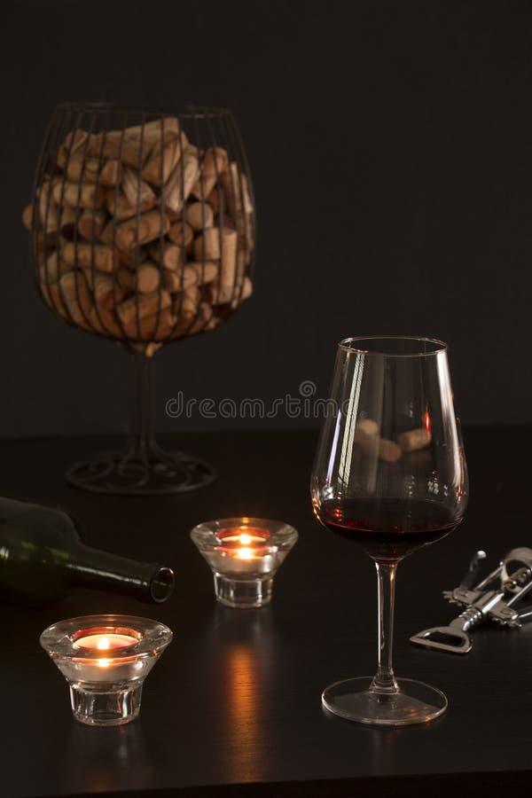 Szkło wino w przedpolu z pustą butelką, corkscrew i korkami od butelek wśrodku wazowego pozorowania szkło, zdjęcie royalty free