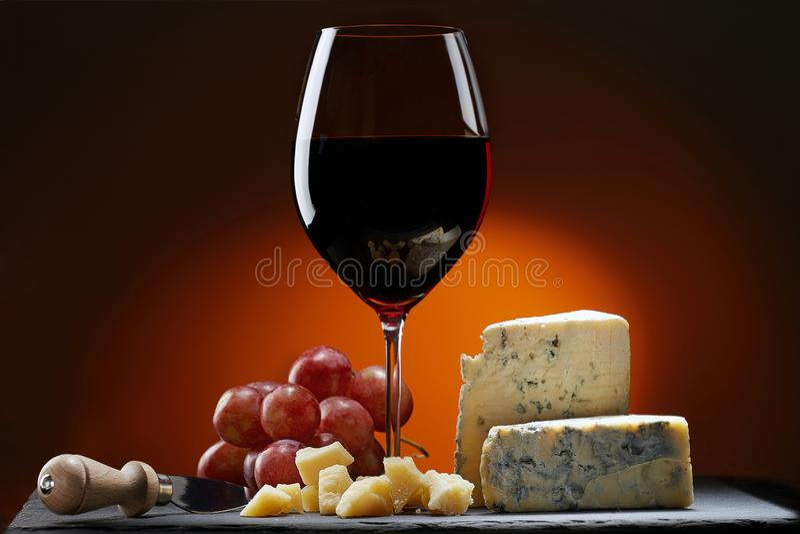 Szkło wino z winogronami i kawałkiem ser z foremką, Parmezański ser i sera nóż, zdjęcia stock
