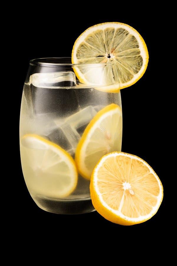 Szkło woda i cytryna odizolowywający na czarnym tle zdjęcia royalty free