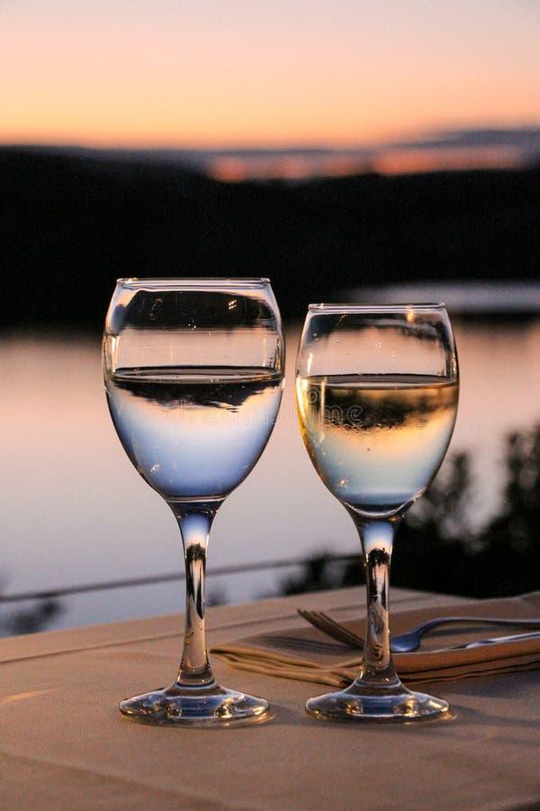Szkło woda i szkło wino na stole w restauraci z zmierzchu widokiem przy jeziornym maratonem, Grecja obraz stock