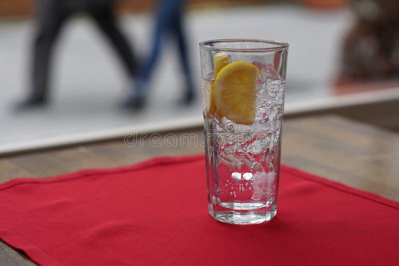 Szkło woda mineralna i plasterek cytryna na stole fotografia stock