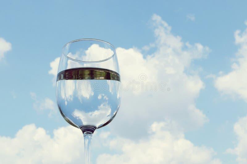 Szkło woda, przejrzysty, z odbiciem, przeciw niebu z chmurami zdjęcia royalty free