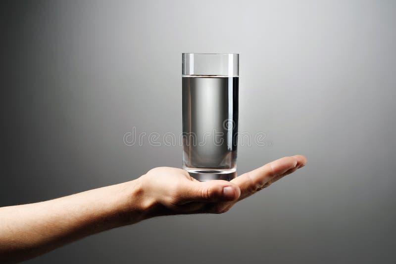 Szkło woda trzyma za ręce przeciw szaremu tłu zdjęcie royalty free