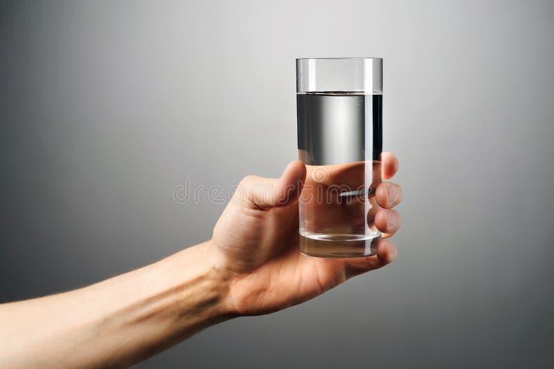 Szkło woda trzyma za ręce przeciw szaremu tłu obrazy royalty free