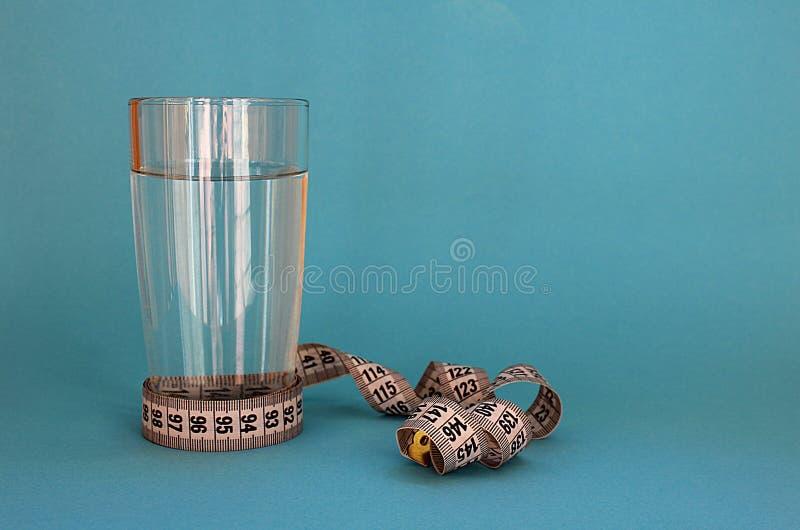 Szkło woda z centymetrową taśmą wirował dietę na wodzie obrazy royalty free