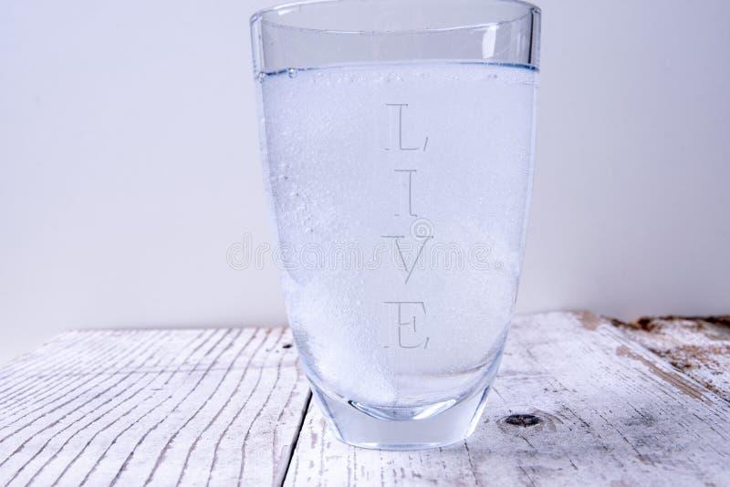 Szkło wodne ze słowem żywa zdjęcie stock