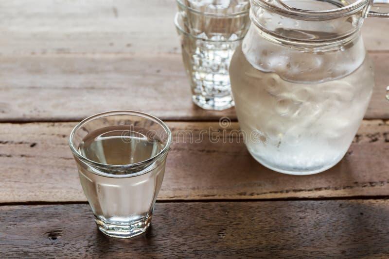 Szkło wody i miotacza szkło na drewnianym stole fotografia royalty free