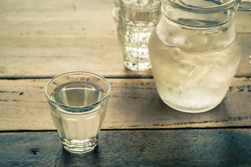 Szkło wody i miotacza szkło na drewnianym stole zdjęcie royalty free