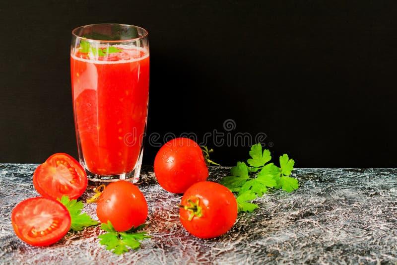 Szkło z świeżym pomidorowym sokiem, ziele i pomidorami na czarnym tle, kosmos kopii zdjęcie royalty free