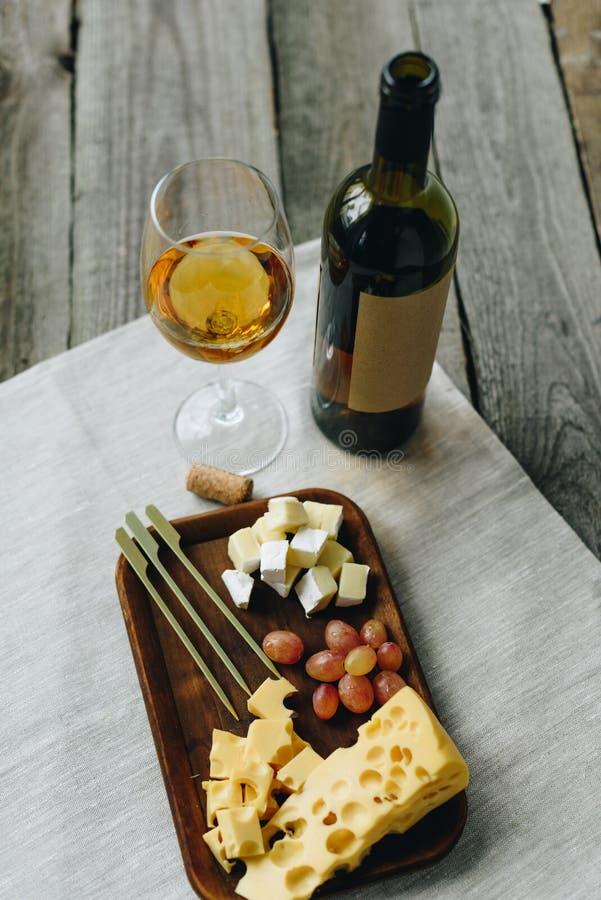 Szkło z białym winem i talerzem z serem i winogronami na drewnianym obrazy royalty free