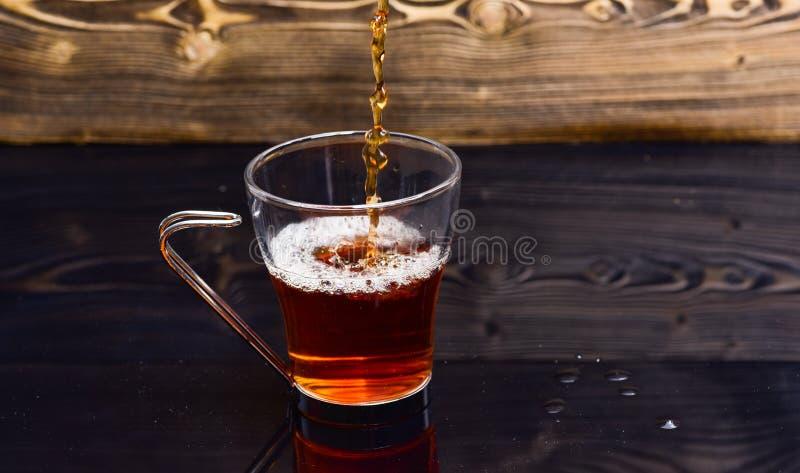 Szkło z herbacianym dolewaniem z cieczem z pluśnięciami i kroplami woda Browarniany herbaciany pojęcie Filiżanki dolewanie z wodą obraz stock