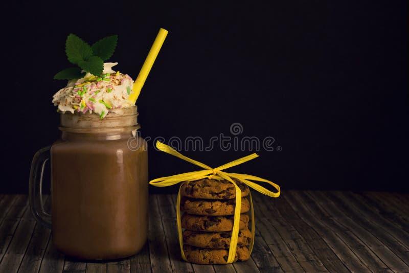 Szkło z kakao i batożącymi ciastkami śmietanki i sterty obraz royalty free