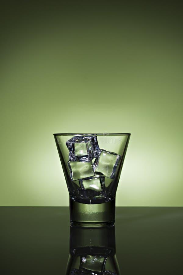 Szk?o z kostka lodu na zielonym tle zdjęcia royalty free