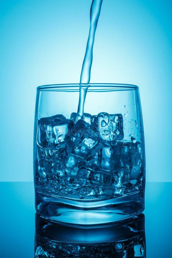 Szkło z lodem, dynamiczny pluśnięcie strumień wody pitnej nalewa wodę w fotografię dla wody pitnej, nadmiara i odpady szklanych,  zdjęcie royalty free