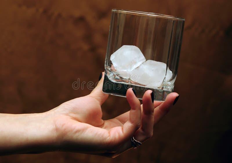 Szkło z lodem w ręce zdjęcie royalty free
