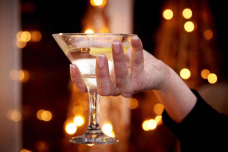 Szkło z Martini w żeńskiej ręce na ciemnym tle z bokeh fotografia stock