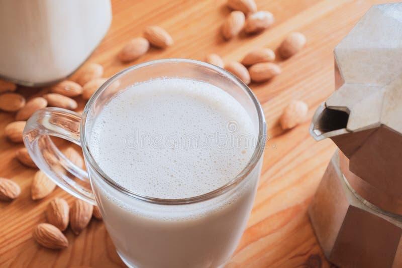 Szkło z mleka migdałowego i browarka do kawy na drewnianym stole zdjęcie royalty free