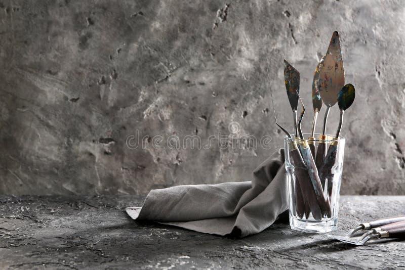 Szkło z paleta nożami na popielatym textured tle obraz royalty free