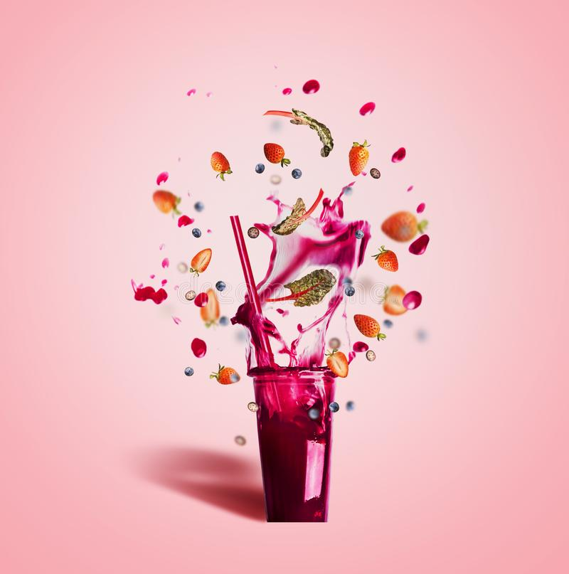 Szkło z pić słomę i purpury bryzgamy lato napój: smoothie lub sok z latającymi jagoda składnikami na menchiach zdjęcia royalty free