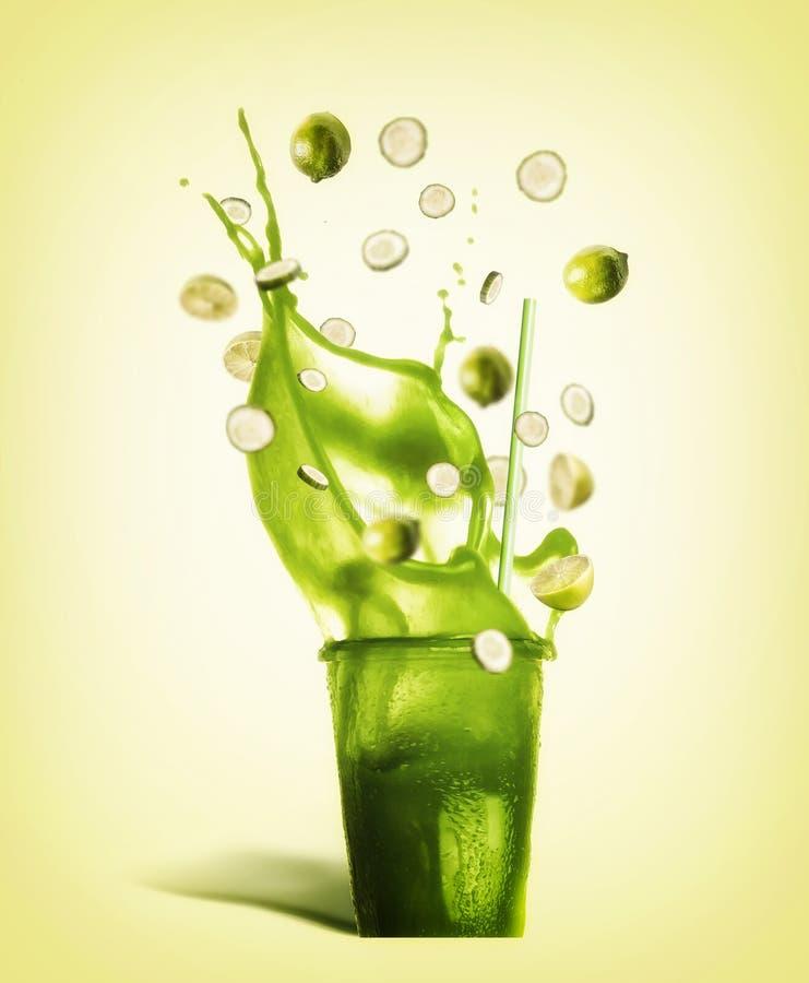 Szkło z pić słomę i zielonego pluśnięcia lata napój: smoothie, sok lub lemoniada z latającymi składnikami, zdjęcie royalty free